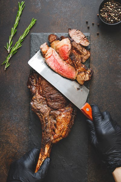Man in black gloves cuts dry-aged marble beef steak Tomahawk. Top view, dinner concept.