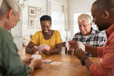 Mature friends playing cards at home