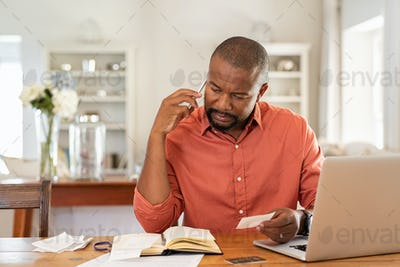 Worried man with bills call the bank