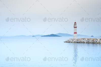 Lonely lighthouse on a stone road in the middle of the sea with views of the mountains and fog