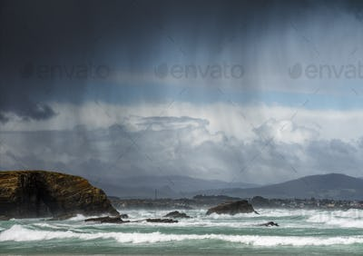 Rain showers blown by the wind between the sea and the cliffs
