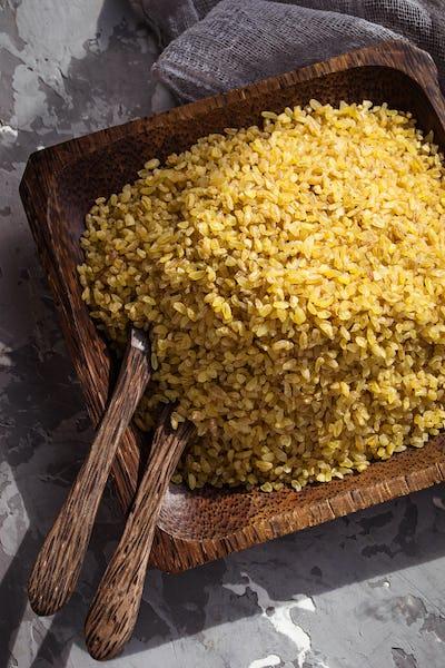 Bulgur wheat grains in a wooden bowl