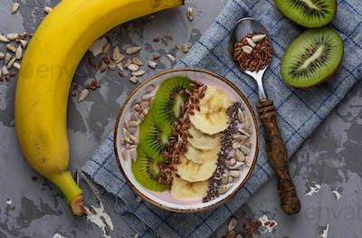 Smoothie in bowl with banana, kiwi, chia, flax and sunflower seeds