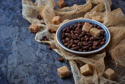 Bowl of coffee beans and brown cane sugar