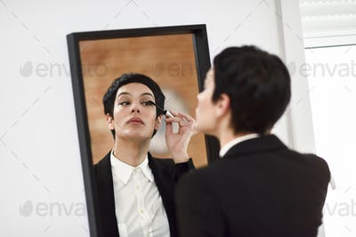 Young woman with very short haircut, putting makeup on in front