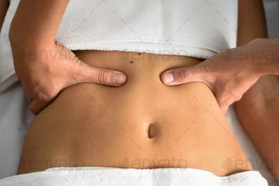 Hands massaging female abdomen.Therapist applying pressure on be