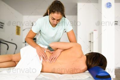 Professional female physiotherapist giving lumbar shoulder massa