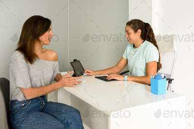 Female physiotherapist explaining diagnosis to her woman patient