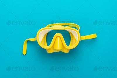 yellow diving mask over blue background with central composition