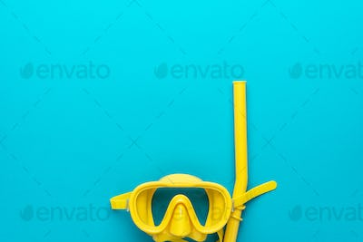 yellow diving mask and snorkel over blue background with copy space
