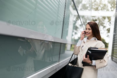 Attractive businesswoman standing and taking call