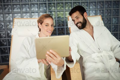 Couple enjoying spa treatments and relaxing with tablet