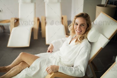 Portrait of beautiful blonde woman relaxing on chair