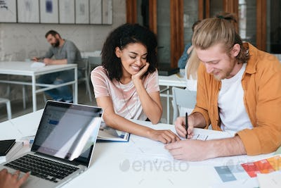 African American lady with curly hair and cool boy with blond hair studying in classroom together