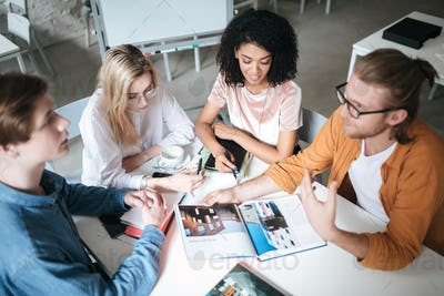 Portrait of young people sitting in office discussing project