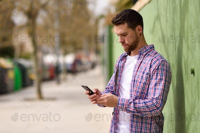Young man looking his smart phone in urban background. Lifestyle