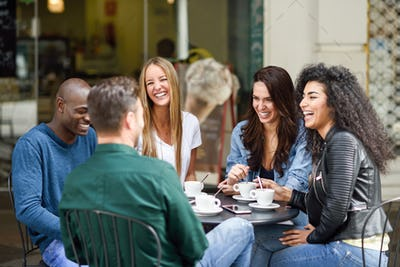 Multiracial group of five friends having a coffee together