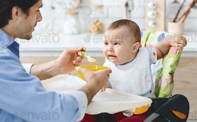 Cute baby frowning nose, doesn't want to eat daddy's meal