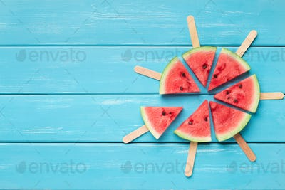 Watermelon popsicles circle on blue wooden background