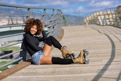 Afro hairstyle woman on roller skates sitting on urban bridge