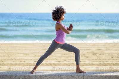 Black woman, afro hairstyle, doing yoga in warrior asana in the