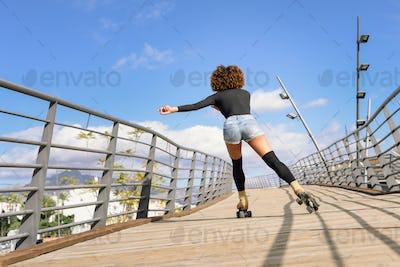 Rear view of black woman on roller skates riding on urban bridge