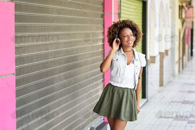 Young black woman, afro hairstyle, in urban street with headphon