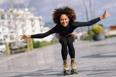 Black woman on roller skates riding outdoors on urban street
