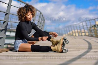 Young smiling black girl sitting on urban bridge and puts on ska