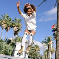 Black woman, afro hairstyle, on roller skates jumping near the b