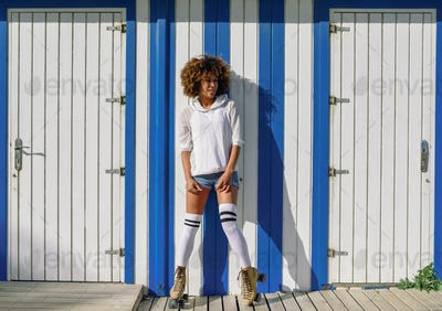 Young black woman on roller skates near a beach hut.