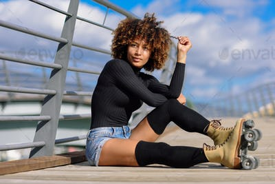 Afro hairstyle woman on roller skates sitting on urban bridge