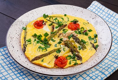 Omelette with asparagus and tomato for breakfast on a wooden background.