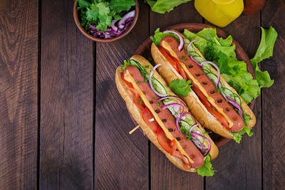Hot dog with  sausage, cucumber, tomato and lettuce on dark wooden background.