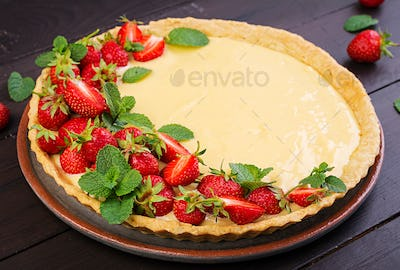 Tart with strawberries and whipped cream decorated with mint leaves on dark background.