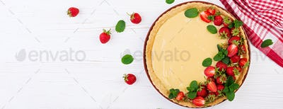 Tart with strawberries and whipped cream decorated with mint lea