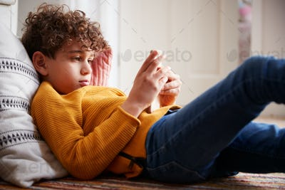 Boy Lying On Floor Of Bedroom Spending Too Much Time Using Mobile Phone