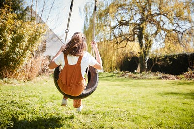 Rear View Of Girl Having Fun On Tyre Swing In Garden At Home