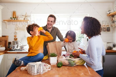 Family Returning Home From Shopping Trip Using Plastic Free Bags Unpacking Groceries In Kitchen