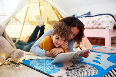 Single Mother Reading With Son In Den In Bedroom At Home