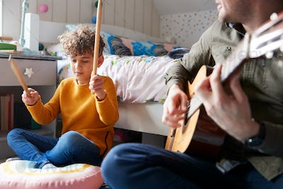 Single Father Playing Guitar With Son Who Drums On Cushion In Bedroom
