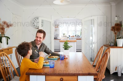 Single Father Sitting At Table Eating Meal With Son In Kitchen At Home