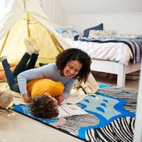 Single Mother Tickling Son As They Read In Den In Bedroom At Home