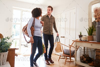 Mature Couple Returning Home From Shopping Trip Carrying Groceries In Plastic Free Bags