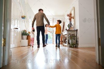 Rear View Of Family Leaving Home On Trip Out With Excited Children