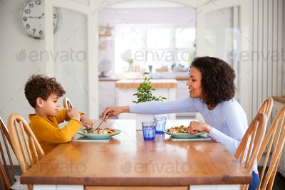 Single Mother Sitting At Table Eating Meal With Son In Kitchen At Home