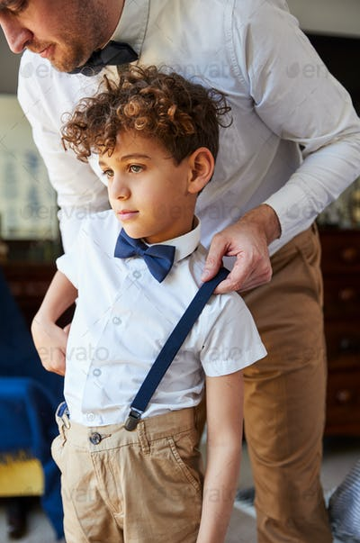 Father And Son Wearing Matching Outfits Getting Ready For Wedding At Home