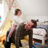 Daughter Riding On Fathers Back As They Play In Den In Bedroom At Home
