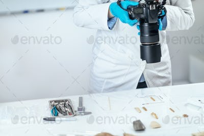 Archaeology Researchers in Laboratory, Documenting Artifacts with Camera