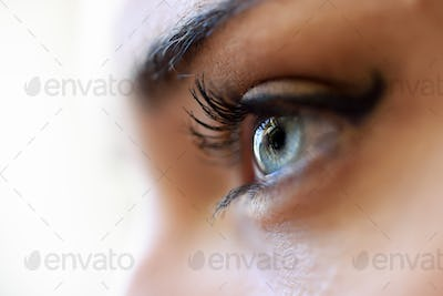 Close-up of young woman's blue eyes with long eyelashes